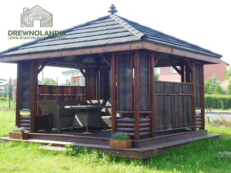 ciemna altana ogrodowa z kanapą stołem i krzesłami