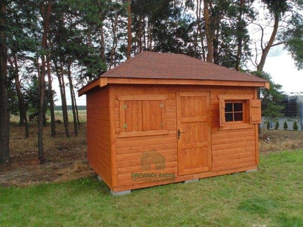 drewutnia z bordowym dachem stojąca na trawie