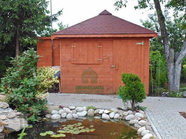 brązowa drewutnia z bordowym dachem stojąca przy drzewie