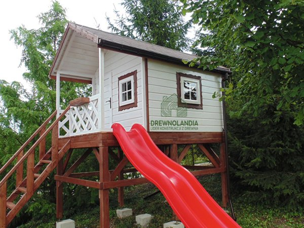 biały domek dla dzieci z czerwoną zjeżdżalnią
