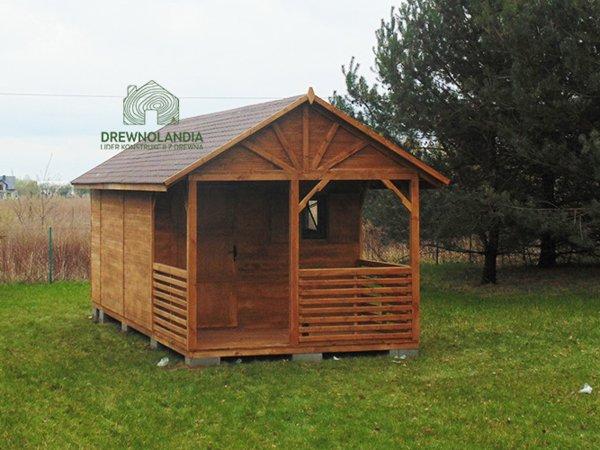 mały domek letniskowy z małym tarasem i bordowym dachem