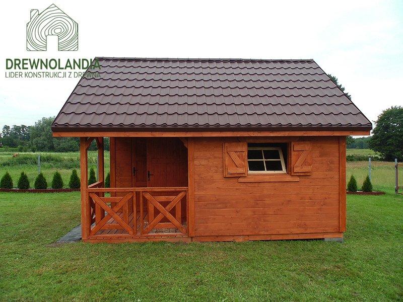 mały domek letniskowy na trawie brązowy z kafelkami na dachu