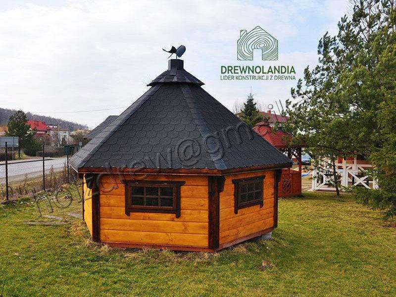 mały domek letniskowy z czarnym dachem na trawie