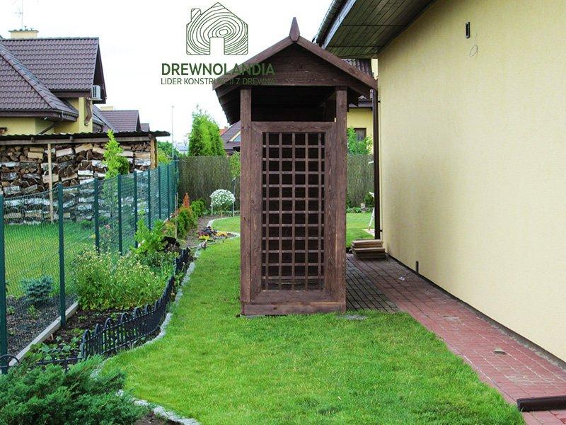 pergola stojąca na trawie przy domu