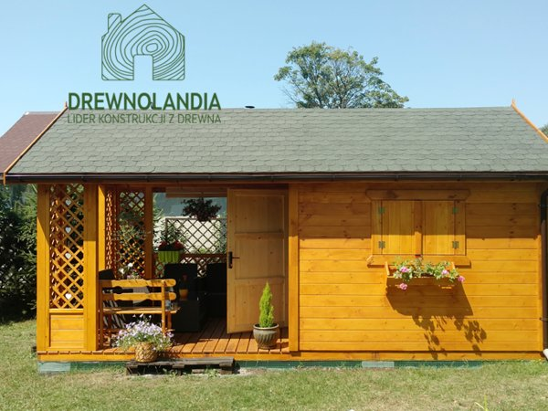 zółty domek drewniany z kwaitami w oknach