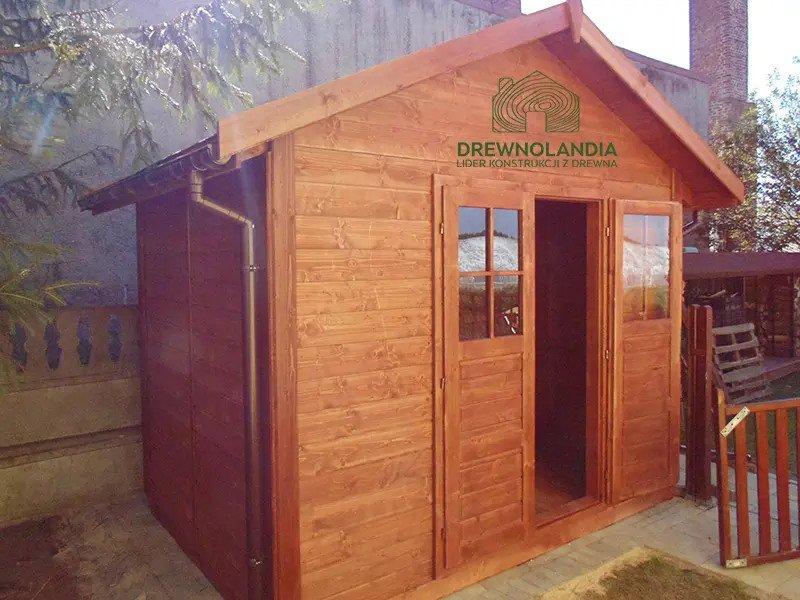 mały domek letniskowy stojący przy domu z otwartymi drzwiami