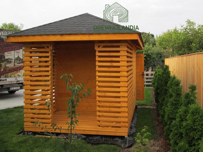 pomarańczowa drewutnia na trawie z ciemnym dachem
