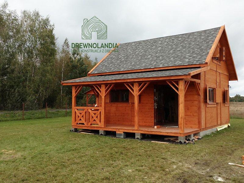 brązowy domek z tarasem i ciemnym dachem