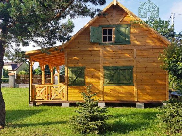 jasnobrązowy domek z zielonymi oknami i tarasem na trawie przy drzewach