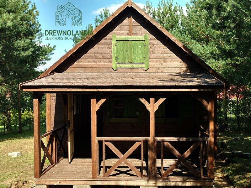 drewniany domek z jednym oknem z zielonymi okiennicami