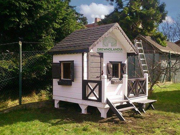 mały biały domek letniskowy dla dzieci z ciemnym dachem na trawie