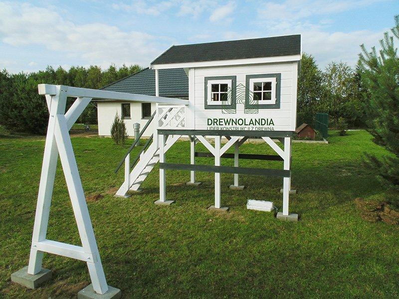 biały domek dla dzieci z miejscem na huśtawkę