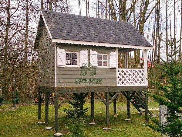 mały domek letniskowy dla dzieci stojący na palach z ciemnym dachem