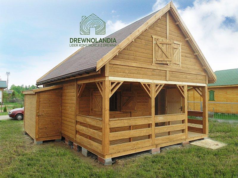 drewniany domek letniskowy z bordowym dachem stojący na trawie
