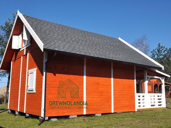 pomarańczowy domek letniskowy na trawie z białymi oknami i tarasem